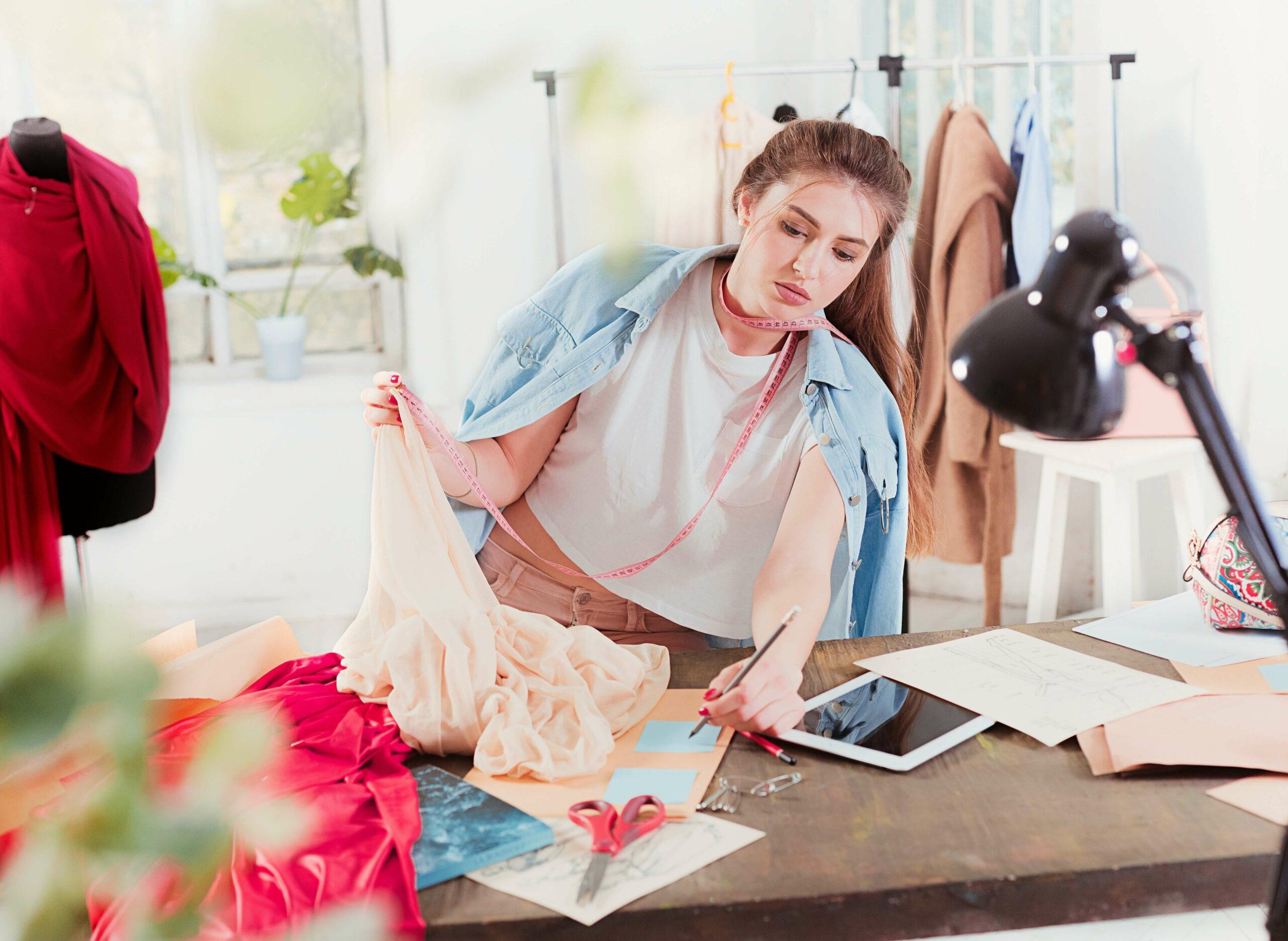 female fashion design student thinking working laptop bright studio environment 1 1 scaled