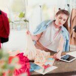 female fashion design student thinking working laptop bright studio environment1